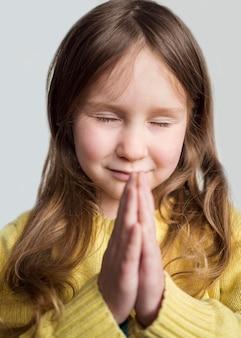 Vooraanzicht van mooie lachende meisje bidden