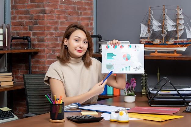 Vooraanzicht van mooie vrouw die diagrammen toont die op kantoor werken