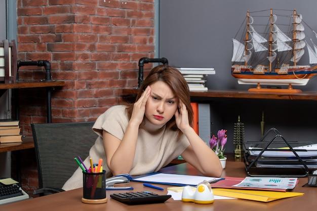 Vooraanzicht van mooie vrouw die haar hoofd vasthoudt met pijn die op kantoor werkt