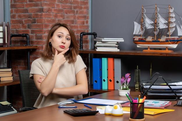 Vooraanzicht van mooie vrouw die hand op haar kin legt die op kantoor werkt