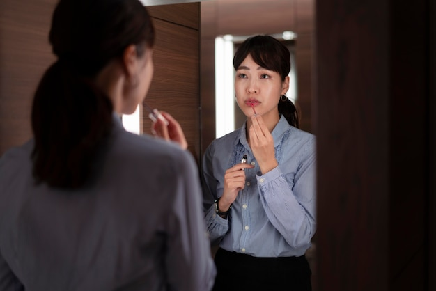 Vooraanzicht van mooie vrouw die in de spiegel kijkt