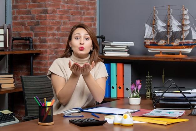 Vooraanzicht van mooie vrouw die kus verzendt die in bureau werkt