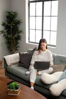 Vooraanzicht van mooie vrouw die op laptop verblijft