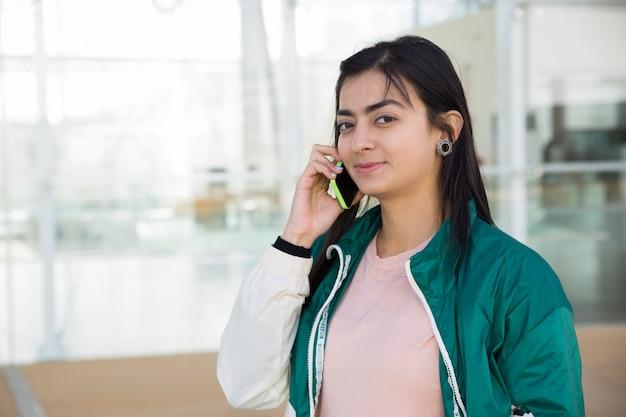 Vooraanzicht van mooie vrouw die op telefoon spreekt, die camera bekijkt