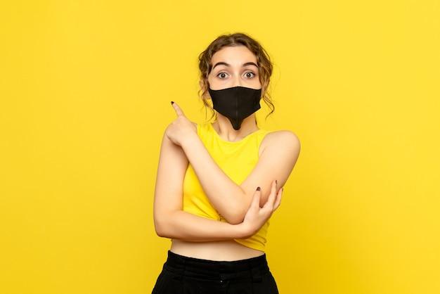 Vooraanzicht van mooie vrouw in zwart masker op geel