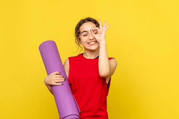 Vooraanzicht van mooie vrouw lachend met paars tapijt op geel