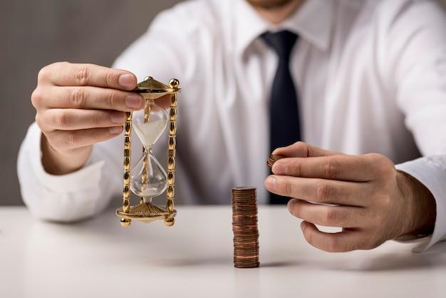 Vooraanzicht van munten en zandloper gehouden door zakenman