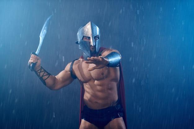 Vooraanzicht van natte romeinse gladiator in ijzeren helm en rode mantel zwaaiend met zwaard. gespierde shirtless spartaans in harnas tijdens gevecht bij regenachtig slecht weer. concept van oude krijger, sparta.