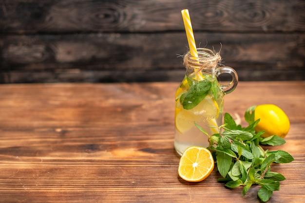 Vooraanzicht van natuurlijk vers detoxwater geserveerd met tube mint en sinaasappel aan de linkerkant op een bruine achtergrond