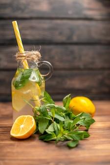 Vooraanzicht van natuurlijk vers detoxwater geserveerd met tube mint en sinaasappel op een bruine achtergrond