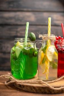 Vooraanzicht van natuurlijke biologische vruchtensappen in flessen geserveerd met buizen op een houten snijplank