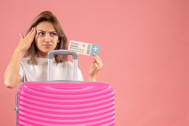 Vooraanzicht van neerslachtig jong meisje met het roze kaartje van de kofferholding