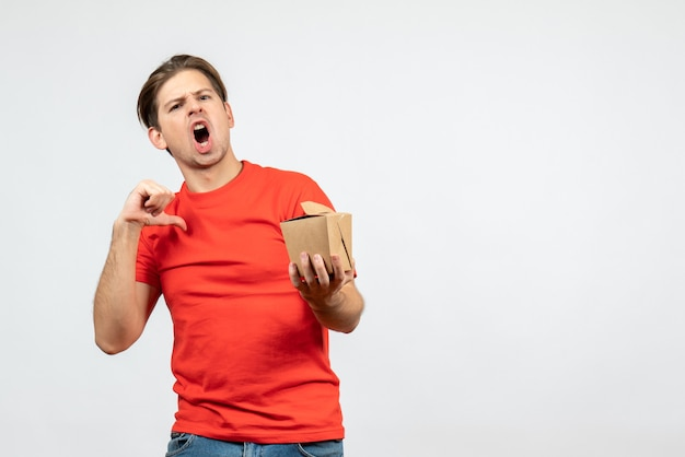 Vooraanzicht van nerveuze jonge kerel in rode blouse die kleine doos houdt die op witte achtergrond richt
