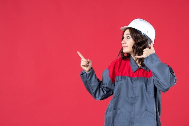 Vooraanzicht van nieuwsgierige vrouwelijke bouwer in uniform met harde hoed en bel me gebaar naar boven op geïsoleerde rode achtergrond