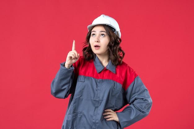 Vooraanzicht van nieuwsgierige vrouwelijke bouwer in uniform met harde hoed en omhoog gericht op geïsoleerde rode achtergrond