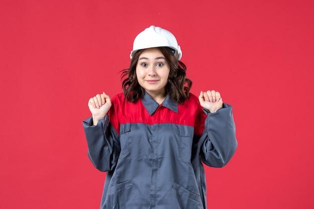 Vooraanzicht van nieuwsgierige vrouwelijke bouwer in uniform met helm op geïsoleerde rode achtergrond