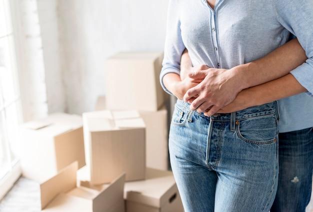 Vooraanzicht van omhelsde paar thuis tijdens het inpakken om te bewegen