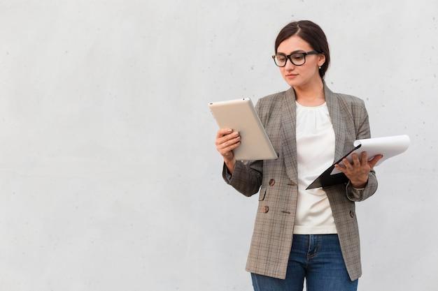 Vooraanzicht van onderneemster buiten met tablet en blocnote