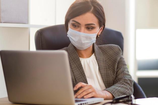 Vooraanzicht van onderneemster met gezichtsmasker die bij bureau werken