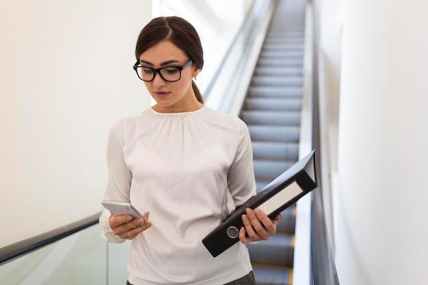 Vooraanzicht van onderneemster met smartphone en bindmiddel