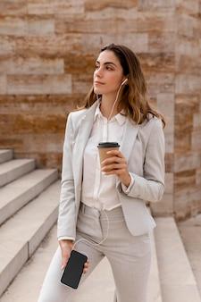 Vooraanzicht van onderneemster met smartphone en koffiekop