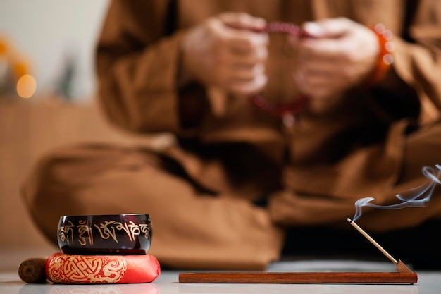Vooraanzicht van onscherpe man mediteren met kralen naast klankschaal
