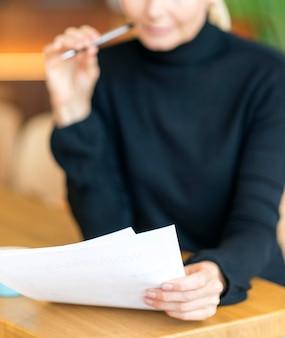 Vooraanzicht van onscherpe oudere vrouw op het werk papieren lezen