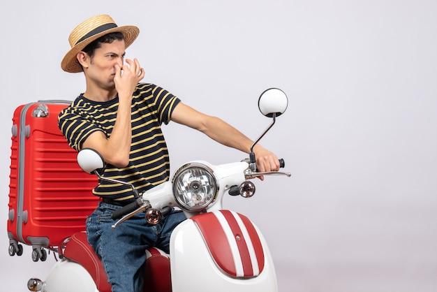 Vooraanzicht van ontevreden jongeman met strooien hoed op bromfiets met neus