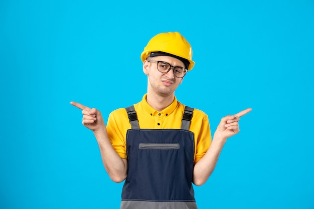 Vooraanzicht van ontevreden mannelijke werknemer in geel uniform op blauwe muur