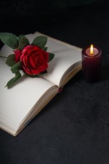 Vooraanzicht van open boek met kaars en rode bloem op zwart