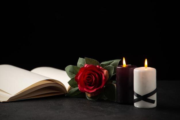 Vooraanzicht van open boek met kaarsen en roos op zwart