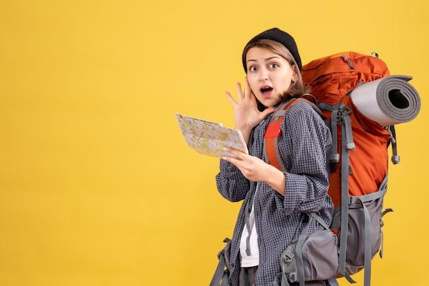 Vooraanzicht van opgewonden jonge reiziger met de kaart van de rugzakholding