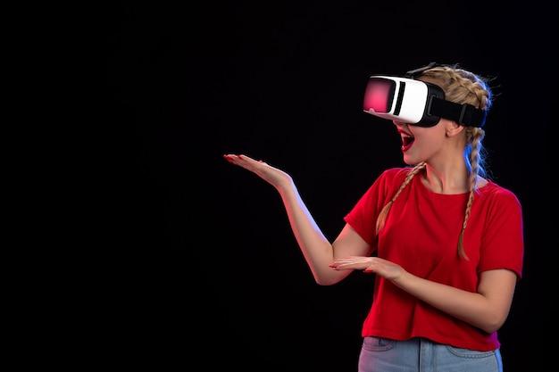 Vooraanzicht van opgewonden jonge vrouw die vr speelt op donkere echografie-speltechnologie