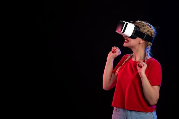 Vooraanzicht van opgewonden jonge vrouw die vr speelt op donkere echografie-tech-game
