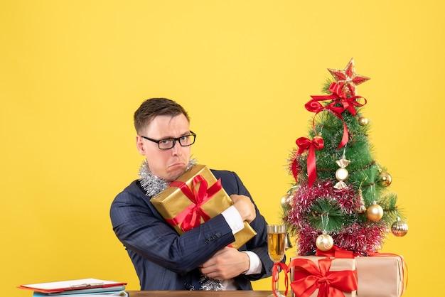 Vooraanzicht van opgewonden man die zijn geschenk stevig vasthoudt aan de tafel in de buurt van de kerstboom en geschenken op gele muur kopie ruimte