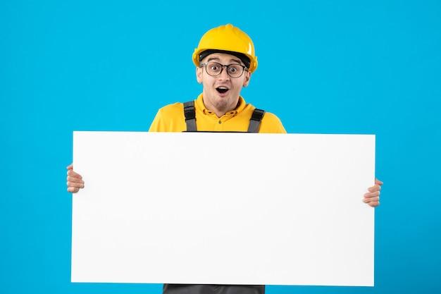 Vooraanzicht van opgewonden mannelijke bouwer in geel uniform met plan blauwe muur
