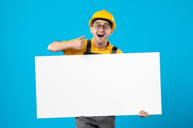 Vooraanzicht van opgewonden mannelijke bouwer in geel uniform op blauw oppervlak