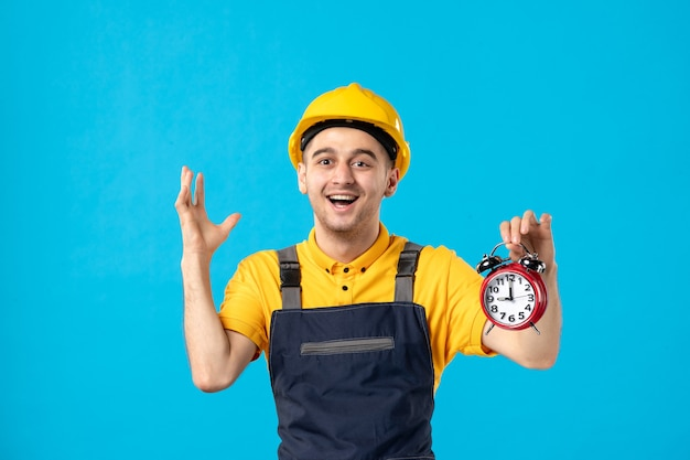 Vooraanzicht van opgewonden mannelijke werknemer in geel uniform met klokken op een blauw oppervlak