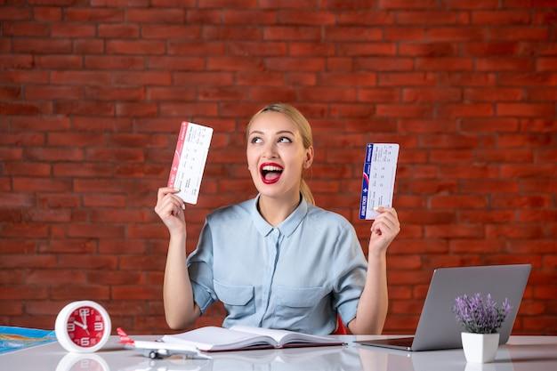 Vooraanzicht van opgewonden reisagent zittend achter haar werkplek met kaartjes global manager agentschap kaart binnenshuis bezetting assistent dienst vlucht toerisme