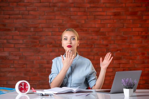 Vooraanzicht van opgewonden reisagent zittend achter haar werkplek toerisme bezetting globale service kaartservice binnenshuis bureau manager assistent