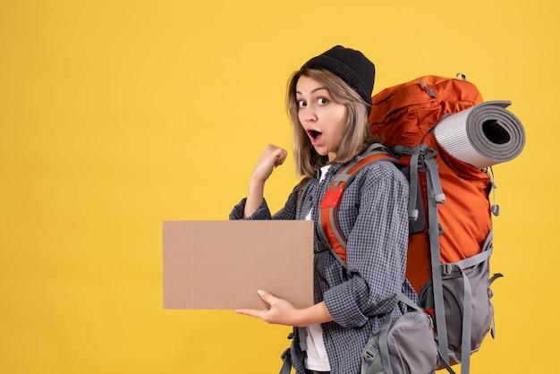 Vooraanzicht van opgewonden reizigersvrouw met het karton van de rugzakholding