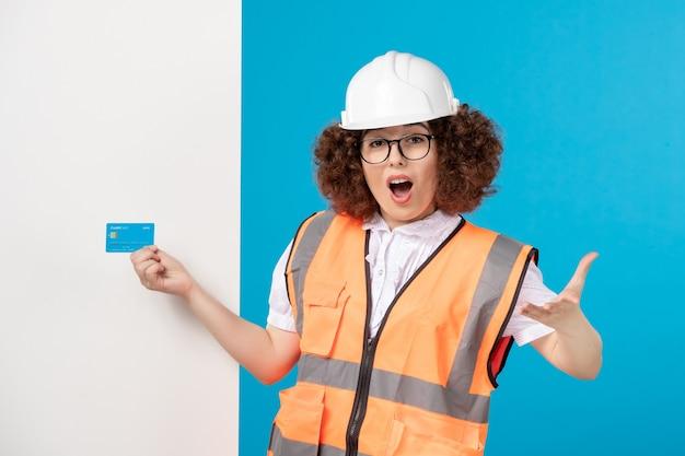 Vooraanzicht van opgewonden werkneemster in uniform op blauwe muur