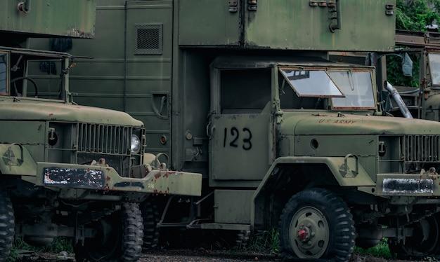 Vooraanzicht van oude gesloopte militaire groene vrachtwagen wil oude lekke band