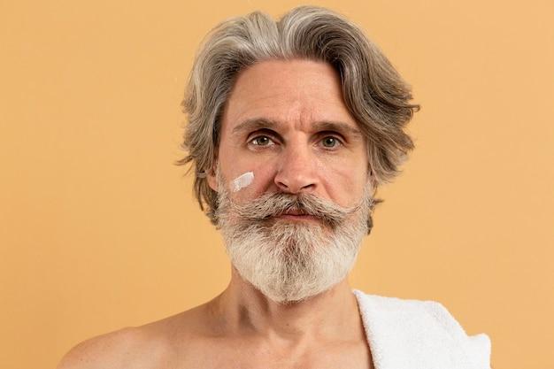 Vooraanzicht van oudere bebaarde man met crème op gezicht