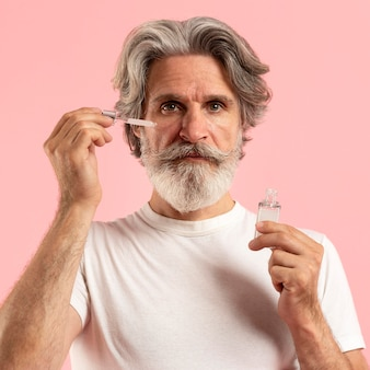 Vooraanzicht van oudere bebaarde man met serum