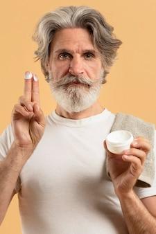 Vooraanzicht van oudere bebaarde man met vochtinbrengende crème
