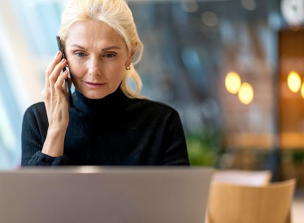 Vooraanzicht van oudere bedrijfsvrouw die aan laptop werkt