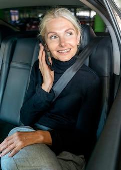 Vooraanzicht van oudere bedrijfsvrouw die de telefoon in auto spreken