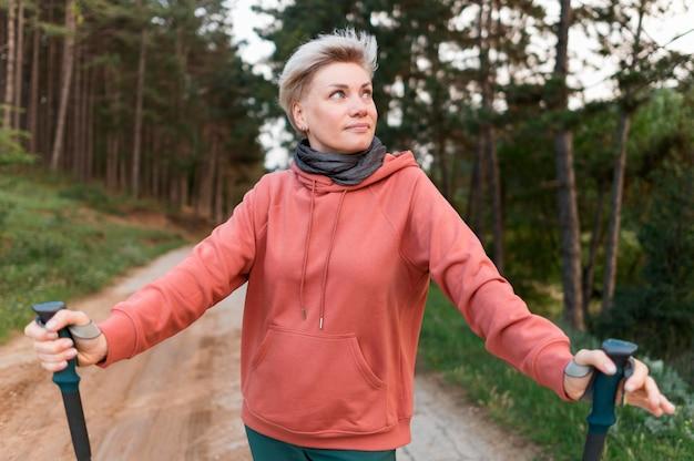 Vooraanzicht van oudere toeristenvrouw in het bos met wandelstokken