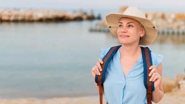 Vooraanzicht van oudere toeristenvrouw met strandhoed